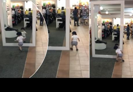 Niño causa ternura al ver su reflejo en el espejo